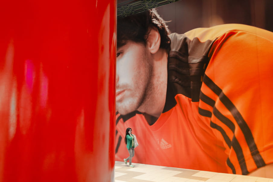 A women on the phone is walking next to a gigantic photograph of a brown-haired man wearing an Adidas orange t-shirt.