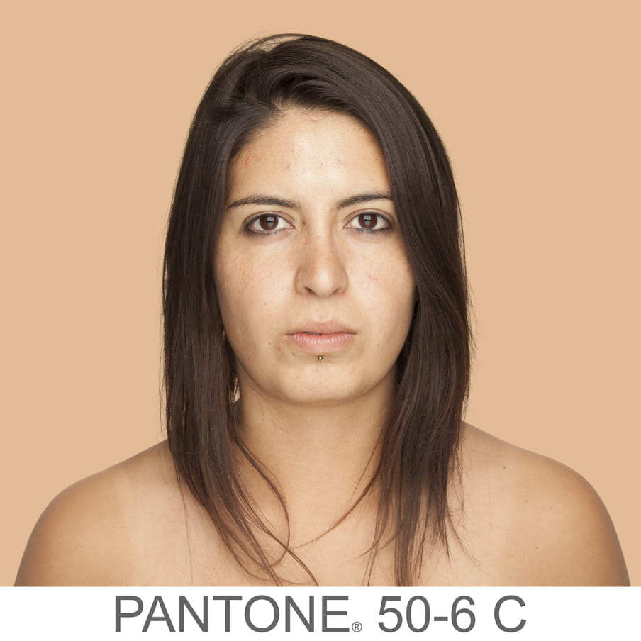 Photographic portrait of a woman brown middle long hair and a labret piercing. The background is a sample of 11 x 11 pixels taken from the nose of the subject and matched with the industrial pallet Pantone®. The pantone color is written out as PANTONE 50-6C.