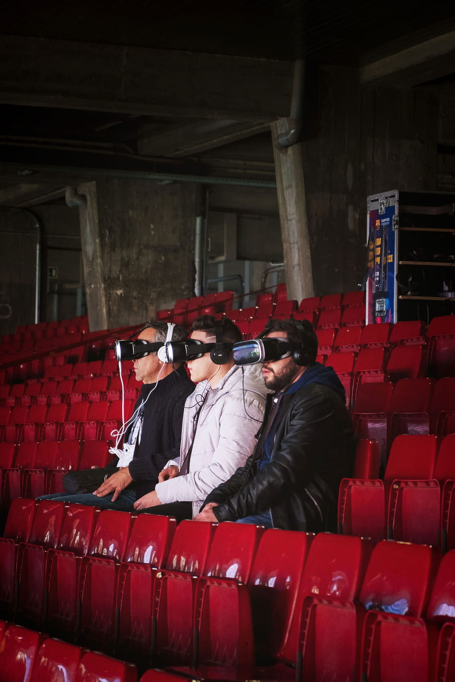 Photo of tree men sit in a football stadium with red chairs experiencing VR googles.