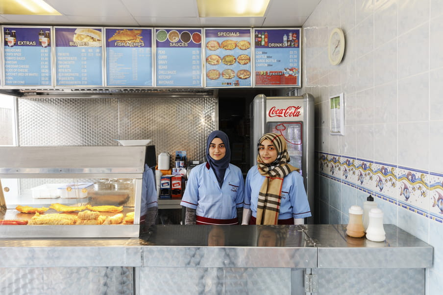 Photo of two girls wearing headscarfs, behind the counter in a fish and chips store