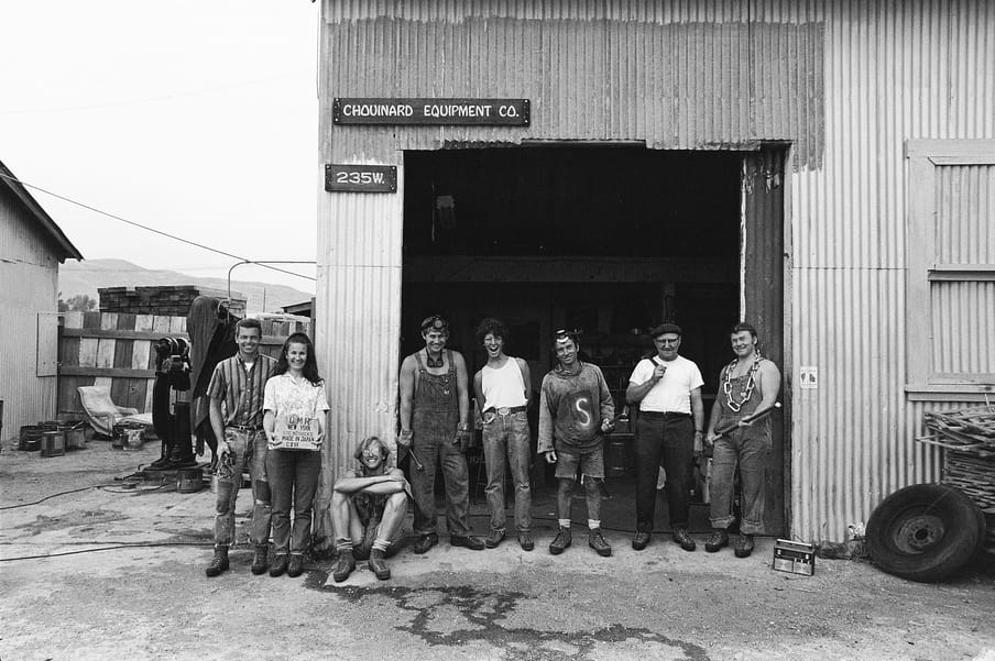 Black and white photo of group of people standing in front of a garage