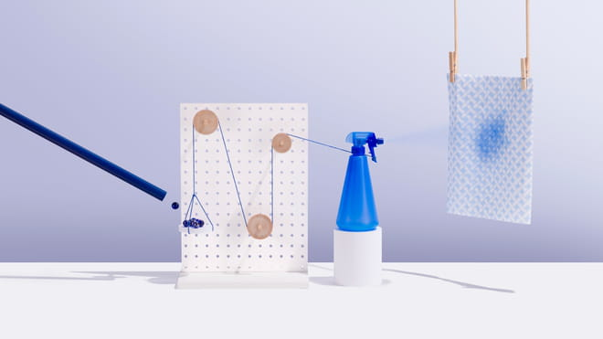 Photo of a blue tube on the left, throwing a small blue ball onto a white, round platform held in place by a blue string. The blue string is whirled around three wooden circular pegs, handing in various places on a vertical, rectangular white wooden board with holes in it. The string is connected on the right to the nozzle of a blue spray bottle. The blue and white kitchen checked kitchen towel hanging to the right of the picture has a blue spray stain on it.