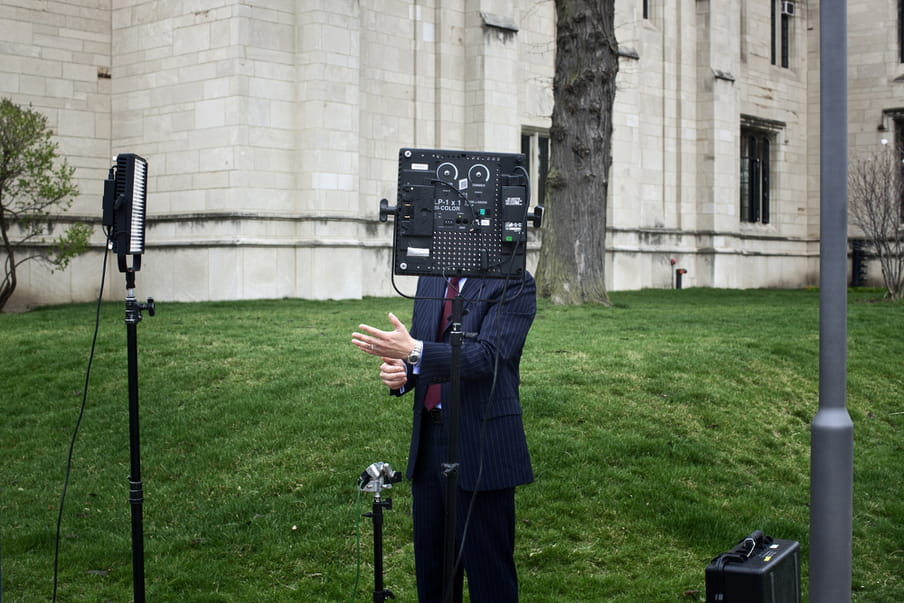 In the background you see an old looking off-white building and a tree's bark; before it, on the grass in the centre, stands a man in a dark suit, tie and wearing a watch, hands gesticulating as if he is talking on camera. His head however is concealed behind a camera on a stand, making it look like he has a camera for a head. Around him lies various professional camera equipment such as a light, microphone, suitcase. There is a lamppost to the right of the image.