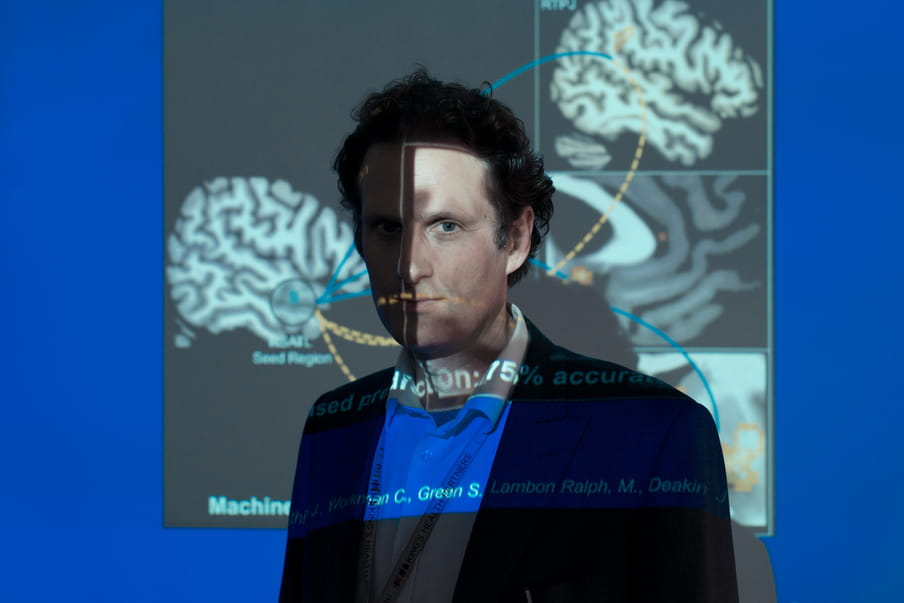 Man with short curtly hair standing in front of a beamer screen, the light of the beamer hitting his face and the screen, deforming the brain graphic on it.