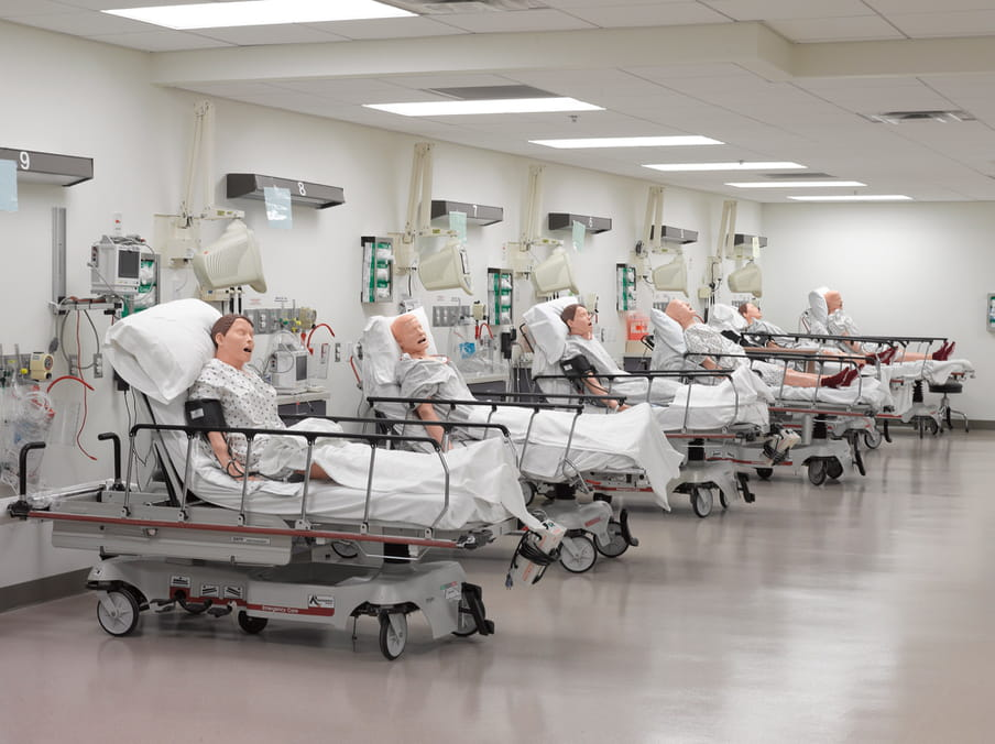 Photo of row with six hospital beds, all occupied by male dolls.