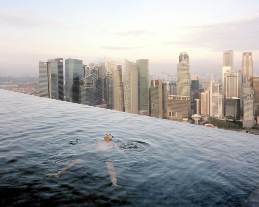 Picture of a man floating in a large pool overlooking a city skyline