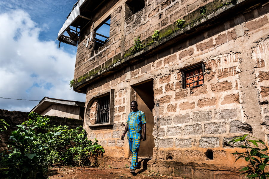 Photo of a man walking out of a house built out of large stone bricks
