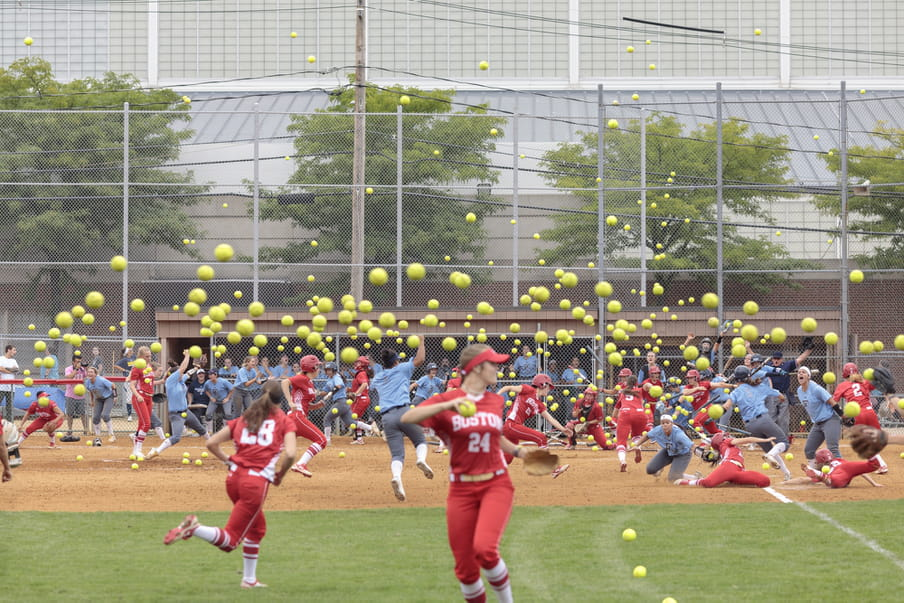 Photo-montage of a softball field, heavily crowded with women playing.
