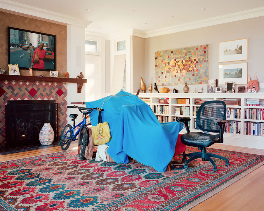 Photo of a living room of a middle or upper class house, with a homeless shelter built from blankets