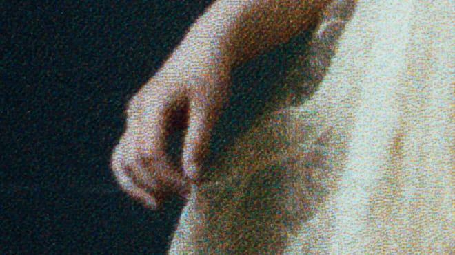 Photo of a girls hand grabbing her dress