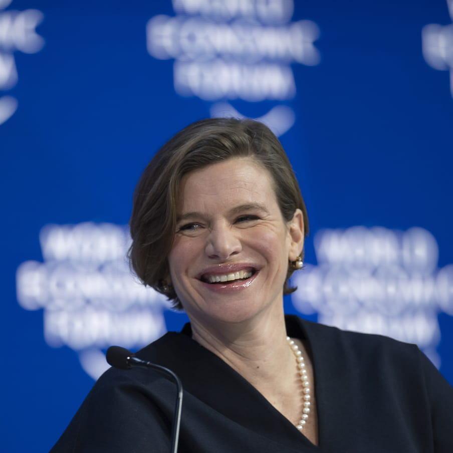 Photo of a woman smiling in front of a blue screen stating 'world economic forum'