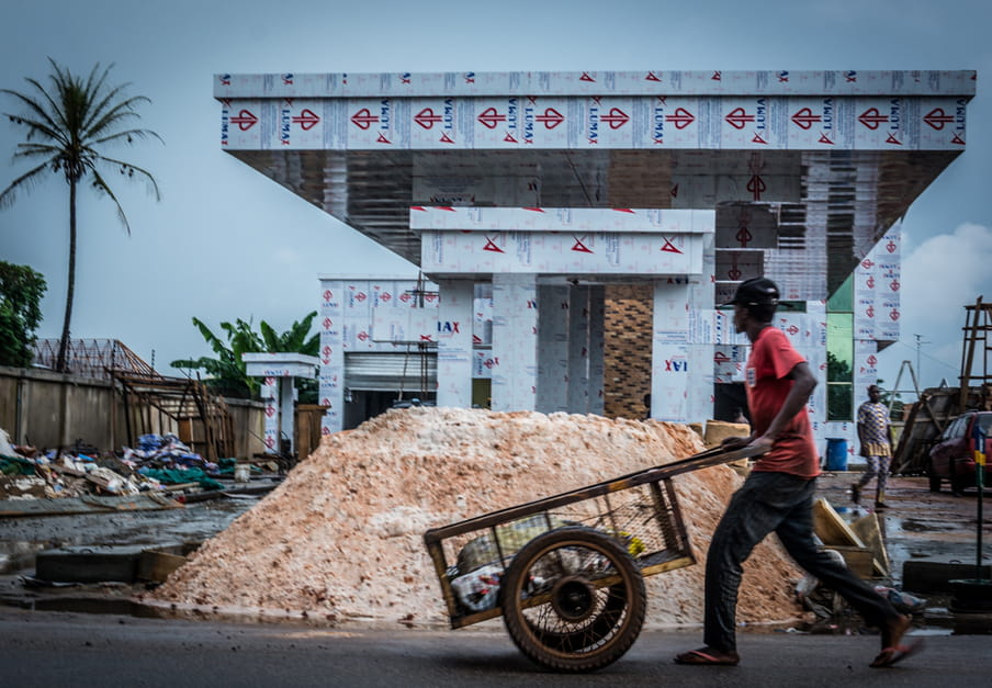 Photo of a man walking with a cart in front of a house under construction
