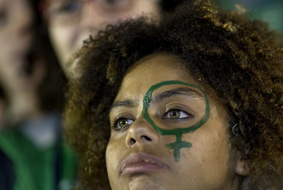 Photo of a girl with dark curly hair and green eyes with a venus sign on her face