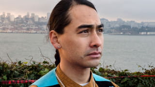 A close up of young man with long dark hair