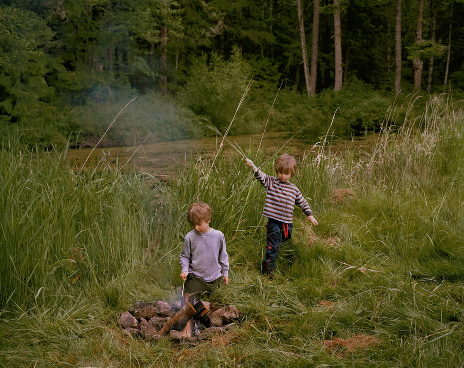 Photo of two boys playing in a field, one is poking a fire with a stick