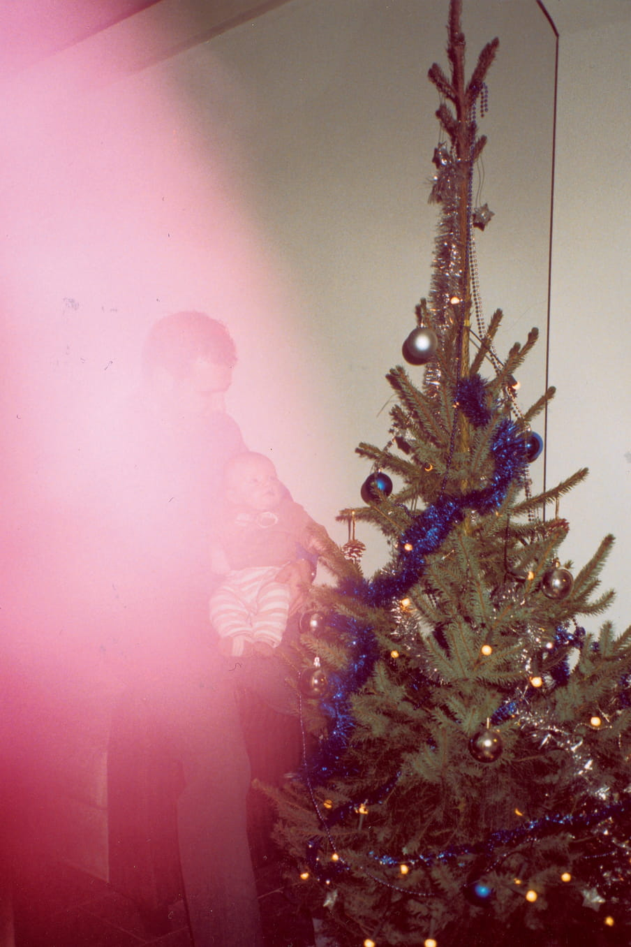 Photograph of a man holding a child next to a christmas three, a red light flare blocking the view of the man with child.