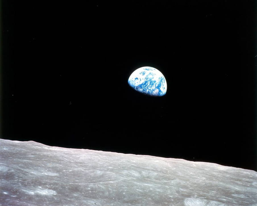 Photo taken from outer space of the blue and white planet Earth, seen hovering above a desolate lunar surface in the foreground.