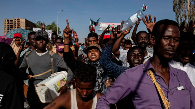 Group of people marching in the streets with Sudanese flags