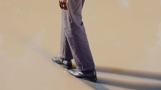 Photo of a person's legs and black shoes, wearing baggy purple suit trousers, and the fingertips, walking through a pool of muddy water