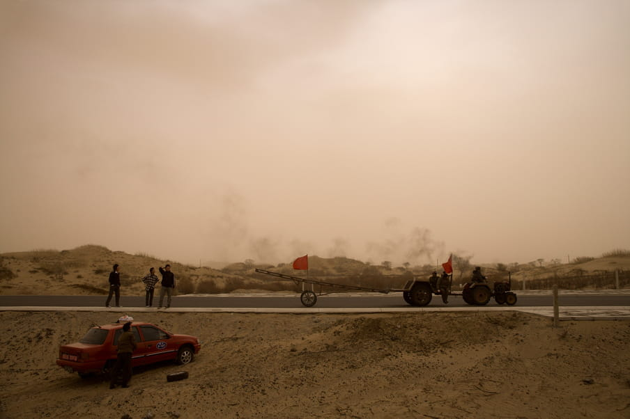 A truck and a car are park on a road in the desert. A few people are standing by.