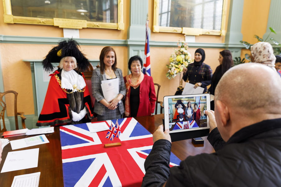 Photo of a woman being photographed in front of the UK flag, holding a paper.