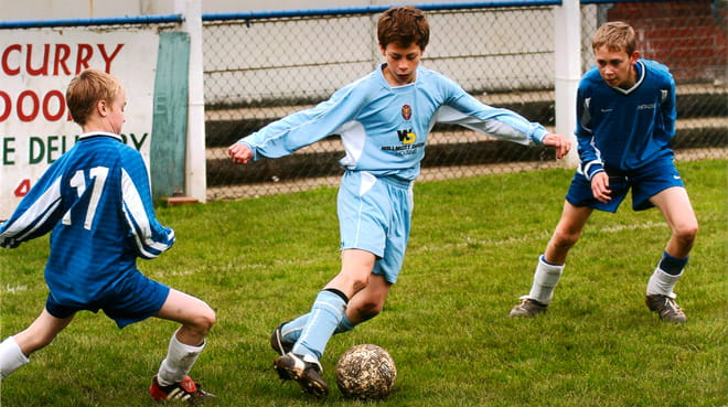 Header image. Photograph of 11-year-old Jamie Lawrence (in the centre of the photo). Three boys playing football in a slightly dated photo; the boy in the centre has arms splayed, and is in a light blue sports long sleeved top and shots, as his right foot is about to kick a muddy football. The other two boys are in darker blue outfits and flank him, eyes on the ball ready to tackle. Behind, we see metallic fencing and a sign saying 'curry'.