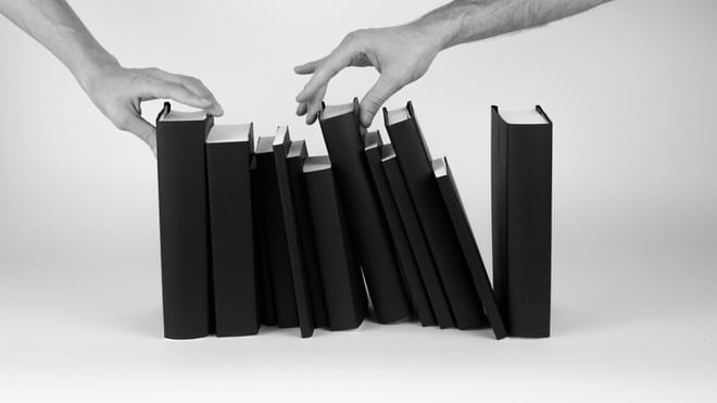 A photograph of two male hands putting together a stack of books.