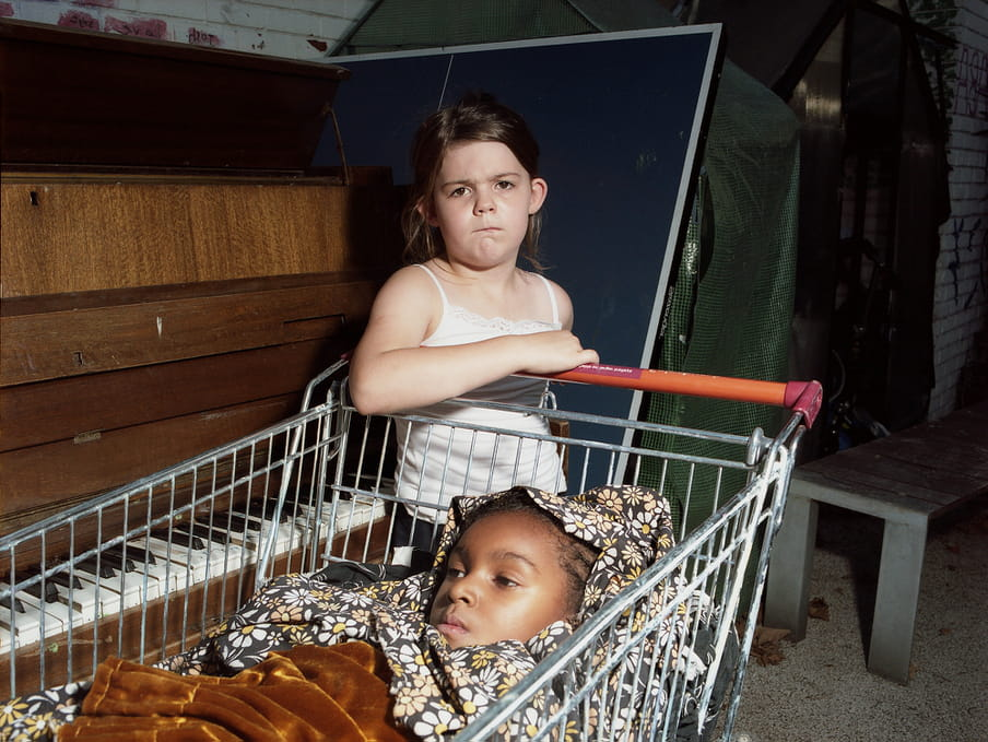 Photo of two kids playing with a shopping cart.