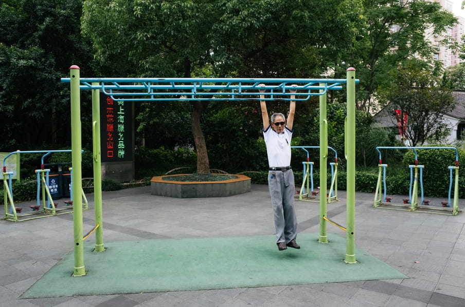 An old man in an outdoor exercise park, swinging from a high bar