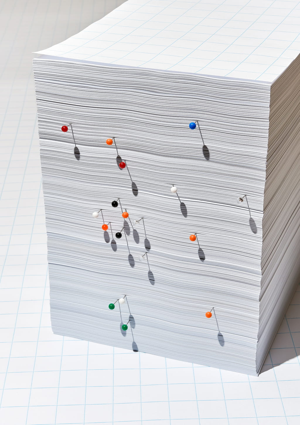 Photograph of a stack of gridded white paper with colourful needles inserted in it.