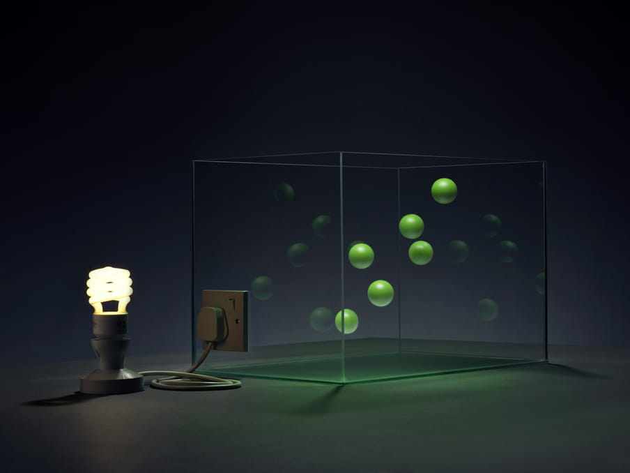 Photo of a lit lamp connected to a glass tank, green little balls floating in it