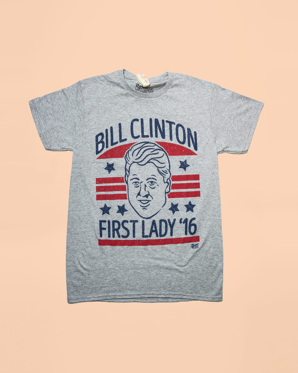 Photo of a grey t-shirt saying 'Bill Clinton, first lady '16' on a salmon coloured background