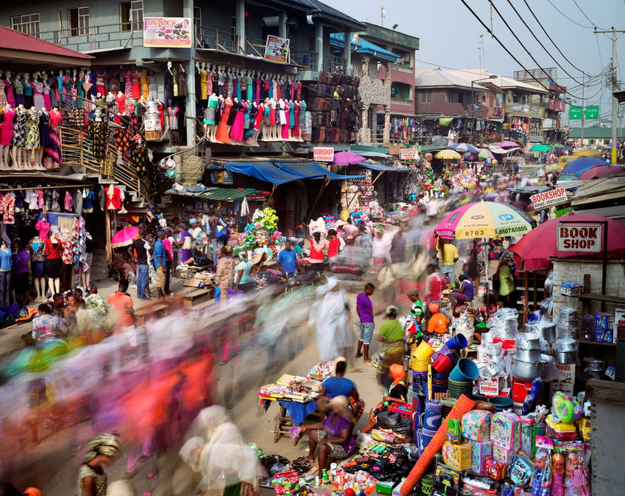 Photo of a busy street with a market on it, colourful merchandise hanging everywhere. It's shot with a high shutterspeed, so people are blurred