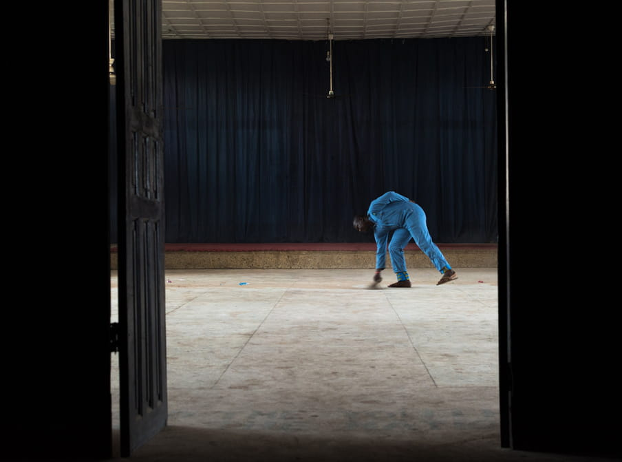 Photo of a man in a blue outfit sweeping the floor