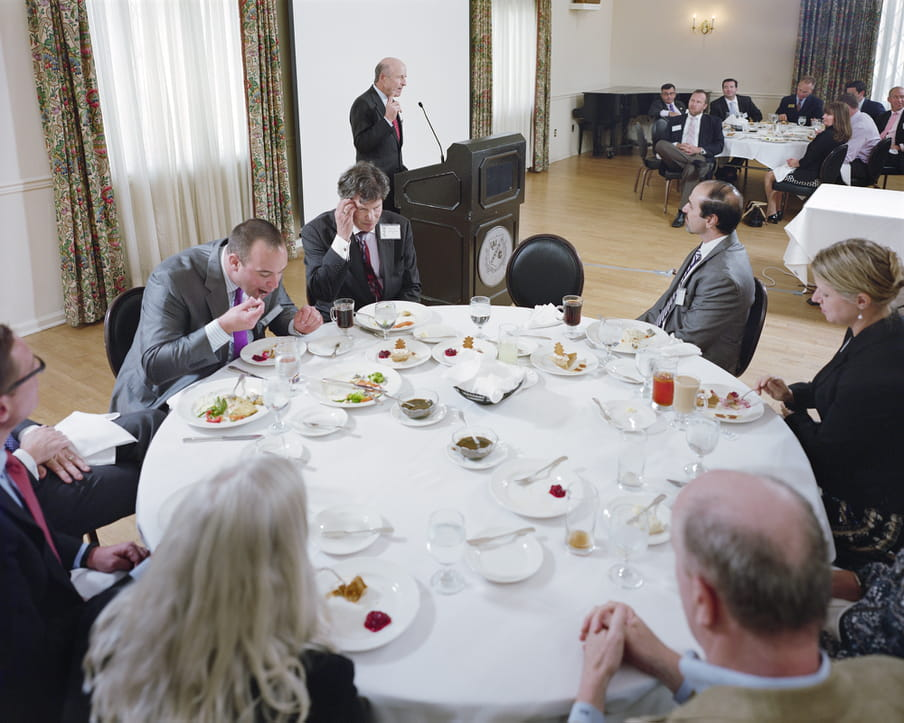 Picture of a round table with a white table cloth, men in suits and women in professional clothing around it. A man is speaking to the crowd.