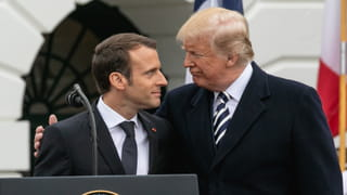 Two men wearing suits, with their arms around each other, are looking at each other, smiling.