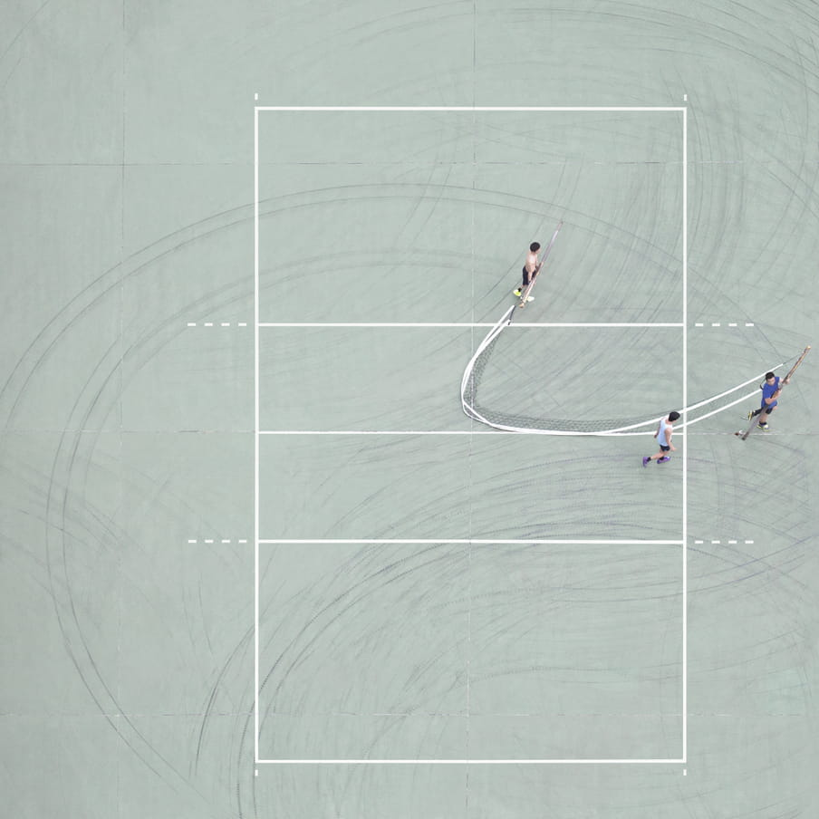 Photograph taken from above of three men transporting a net on a mint green ground court.