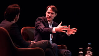 Photo of two men sitting on stage, speaking, one of them gesturing with his hands