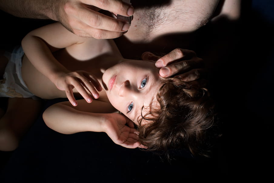 Photo of a young male kid laying on his father's legs waiting for eye's drops medicine.