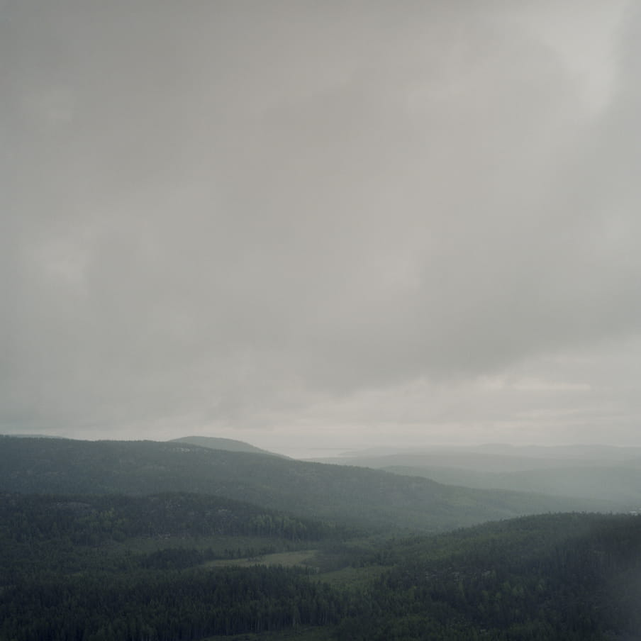 Photograph of a greyish landscape with hills and low hanging grey clouds.