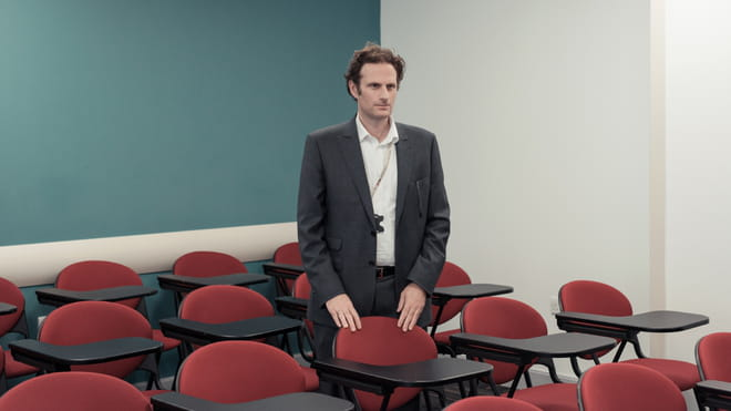 Man wearing a suit standing in a university classroom with his hands on one of the red chairs in it - the wall on the right is white, the one on the left is green.