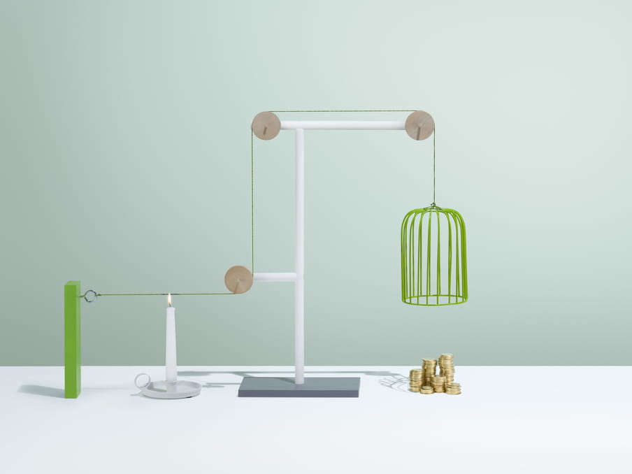 An object looking like a long lampshade made of green wire awaits above five piles of gold coins of different sizes. The lampshade is held in place by green string suspended over three wooden circular pegs connected at various lengths on a white stand. A lit candle stands to the right below the green string, ready to burn the string and drop the cage like object onto the coins.
