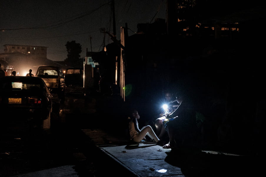 In the darkness of the night, three children are gathered around a source of light hold by one of them. Two are sitting on something unidentified while the third one sits on the ground made of concrete. Some human silhouettes, cars and buildings are visible on the left side of the frame.