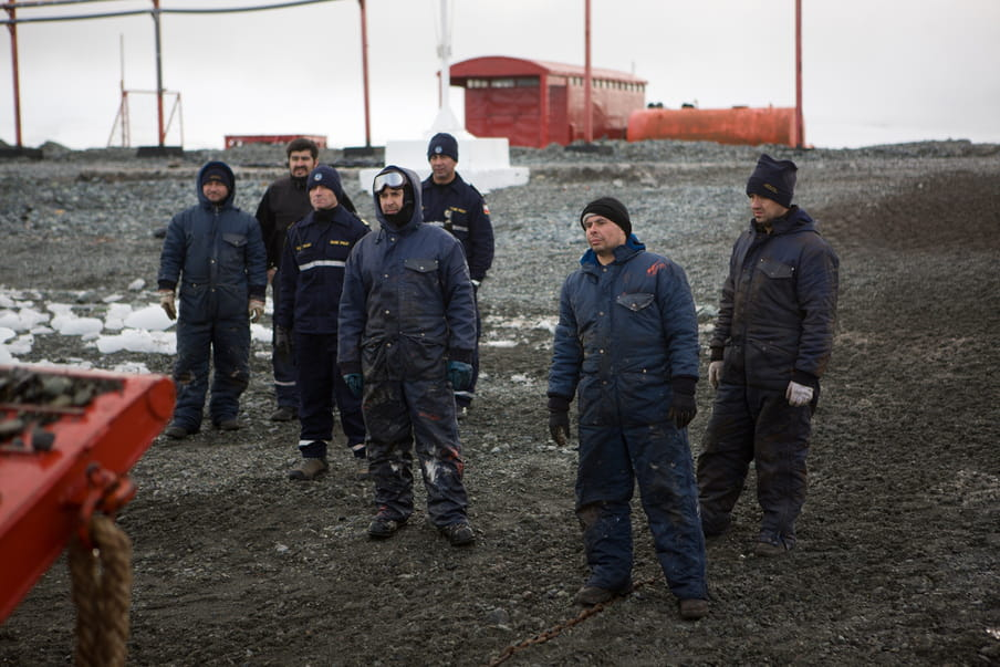 A group of men wearing blue overalls are standing in the gravel.