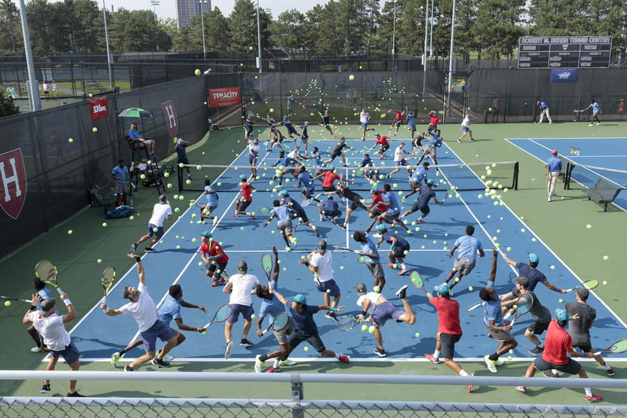 Photo-montage of a blue tennis field, heavily crowded with men playing.