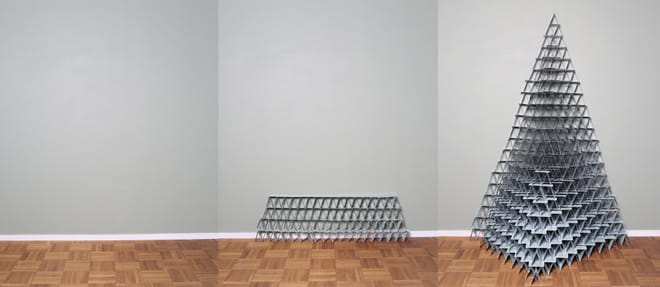 Image composed of three photographs all showing a light grey wall, a white baseboard and a parquetry floor. The photograph on the left is empty. The one in the middle shows a stack of bluish playing cards arranged in a 4 layers flat structure. The one on the right shows a huge pyramid made of the same card deck.
