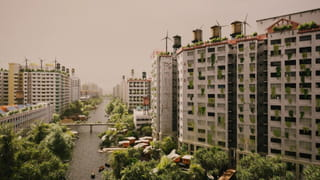 Constructed photo of a cityscape showing large apartment buildings with plants everywhere and windmills on the top of buildings