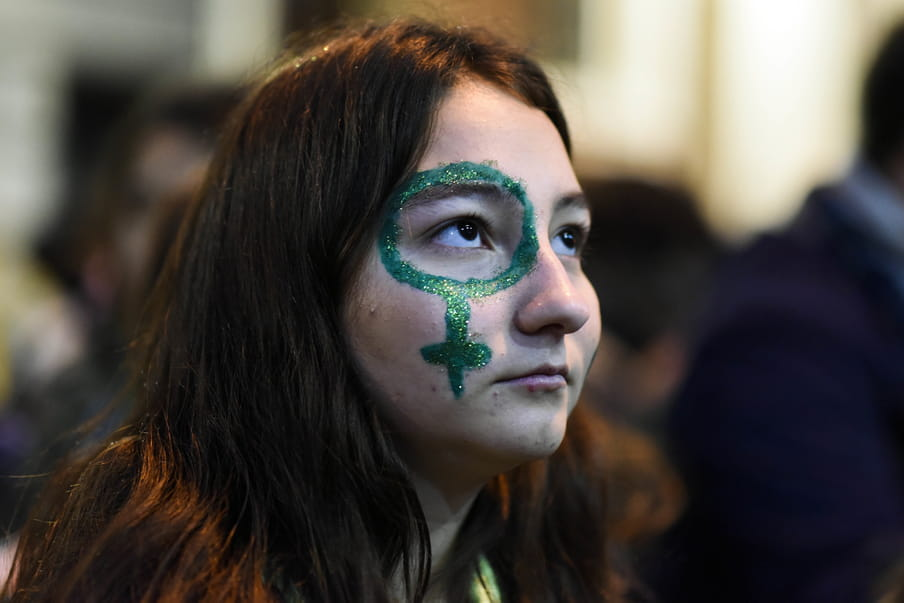 Photo of a girl looking up, a green venus symbol painted in green glitter around her eye