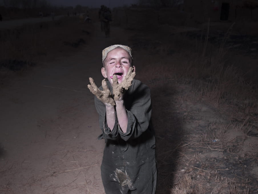 Photo of a kids playing with mud.