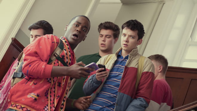 Screenshot from the series Sex Education showing two boys with their boys in their hands. They have a shocked look on their face and are looking at the camera.
